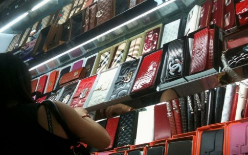 A customer looks at fake foreign brand wallets in a store