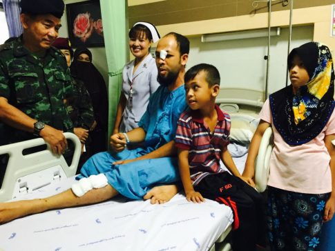 Lt. Gen. Prakarn Chollayuth  visiting a man and his  three children who were injured by a bomb in Narathiwat province.