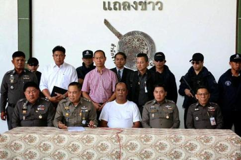 """Police chief Somyot Pumpunmuang, sitting second left, shows Patchuban """"Ko Tong"""" Angchotipan (in white t-shirt) in Bang Khen district, Bangkok Please credit and share this article with others using this link:http://www.bangkokpost.com/news/security/564971/ex-satun-chief-surrenders-to-face-trafficking-charges. View our policies at http://goo.gl/9HgTd and http://goo.gl/ou6Ip. © Post Publishing PCL. All rights reserved."""