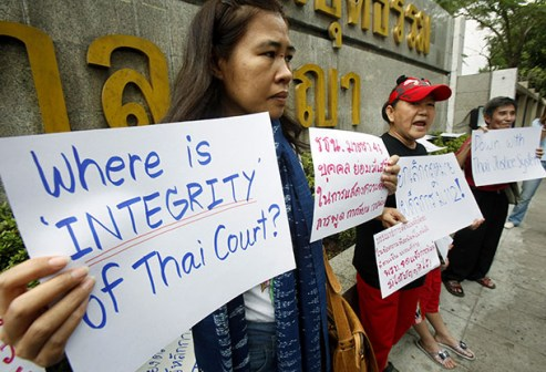 Activists hold signs as they gather in front of the Thai Criminal court during a protest in Bangkok