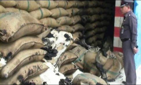 Police Official inspects rotting rice in government warehouse