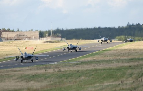 Four F-22 Raptor fighter aircraft taxi after landing