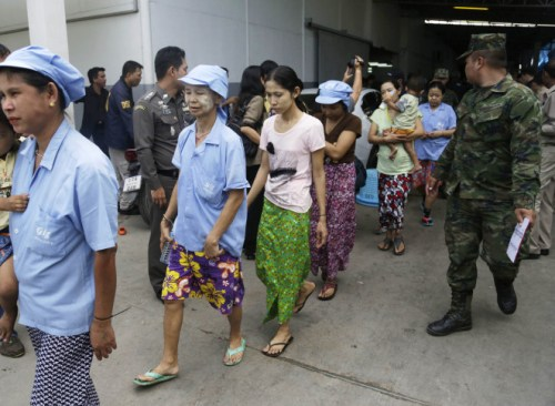 Burmese workers are escorted by soldiers and police officers as they leave a shrimp shed after a raid conducted by Thailand's Department of Special Investigation in Samut Sakhon, Thailand. (AP Photo/Dita Alangkara)