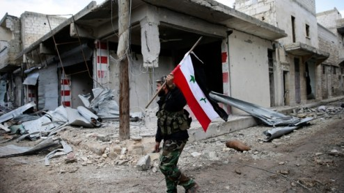 A Syrian army soldier holds up the Syrian national flag as he patrols the east Aleppo