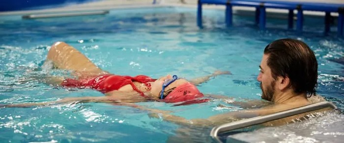 Swim coach teaching adult swimmer how to float