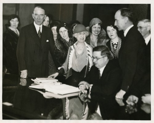 Margaret Haley and several other women stand in a group of men at a desk in 1932