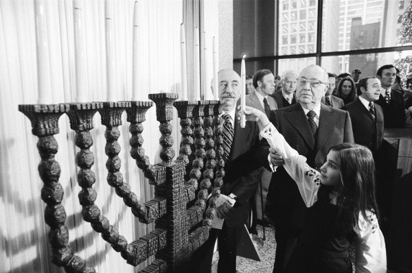 Mayor Richard Daley assists a girl in lighting the menorah at the Civic Center at 50 West Washington Street