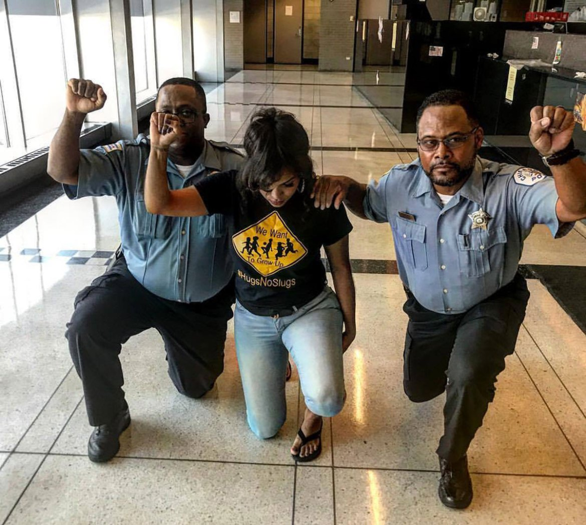 Two African-American Chicago police officers take a knee