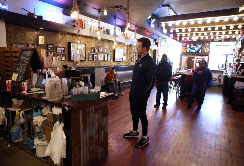 Cort Henson, center, and other customers practice social distancing at Fry the Coop restaurant's West Town location in Chicago while waiting for their orders on Friday, April 10, 2020. The restaurant has pickup and delivery.