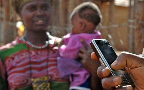 A mobile phone user with an African woman holding a baby in the background