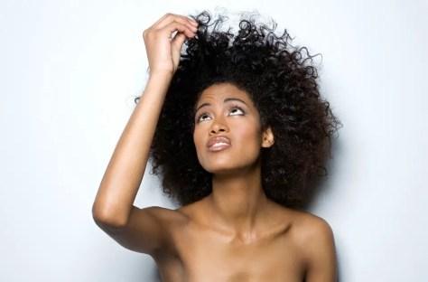 Black Woman looking at damaged natural hair