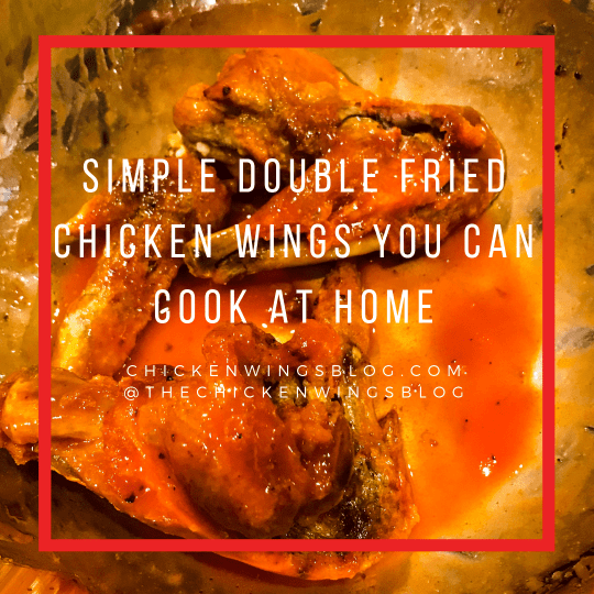 "White text saying, ""Simple Double Fried Chicken Wings You Can Cook At Home"". The text is overlapping a stainless steel bowl of fried chicken in Buffalo sauce."