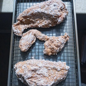 Flour coated chicken pieces on a cooling rack held up in the sunlight to reflect on their change after resting in the fridge for several hours