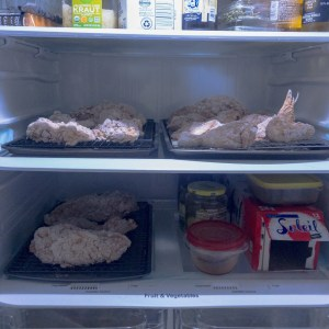Flour coated chicken pieces resting on cooling racks on shelves of a refrigerator filled with other grocery items
