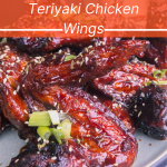 "Depp mahogany brown fried teriyaki flavored chicken wings on a plate with an orange text box with white writing that says ""Unforgettable Teriyaki Chicken Wings"""