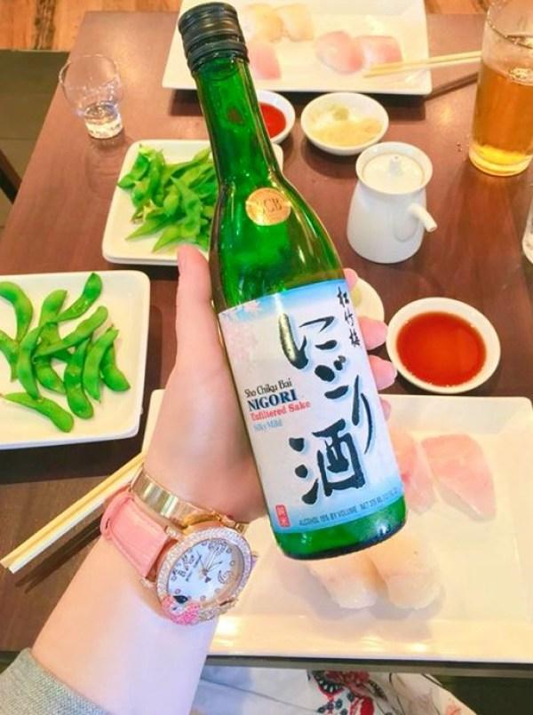 Me holding a bottle of sake at Sugar Fish