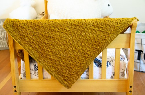 Astrophil Blanket hung over a child's bed in yellow Dk weight yarn.