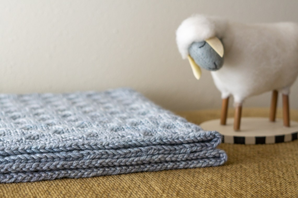 A close up photo of the cast on and bind off rows of a light blue baby blanket, with a toy sheep next to it.