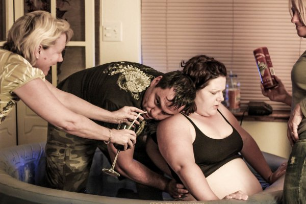 Doula Supports Husband while He Supports Birthing Wife