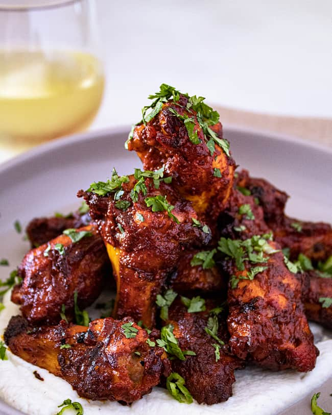 pollo asado rojo wings on a plate with wine
