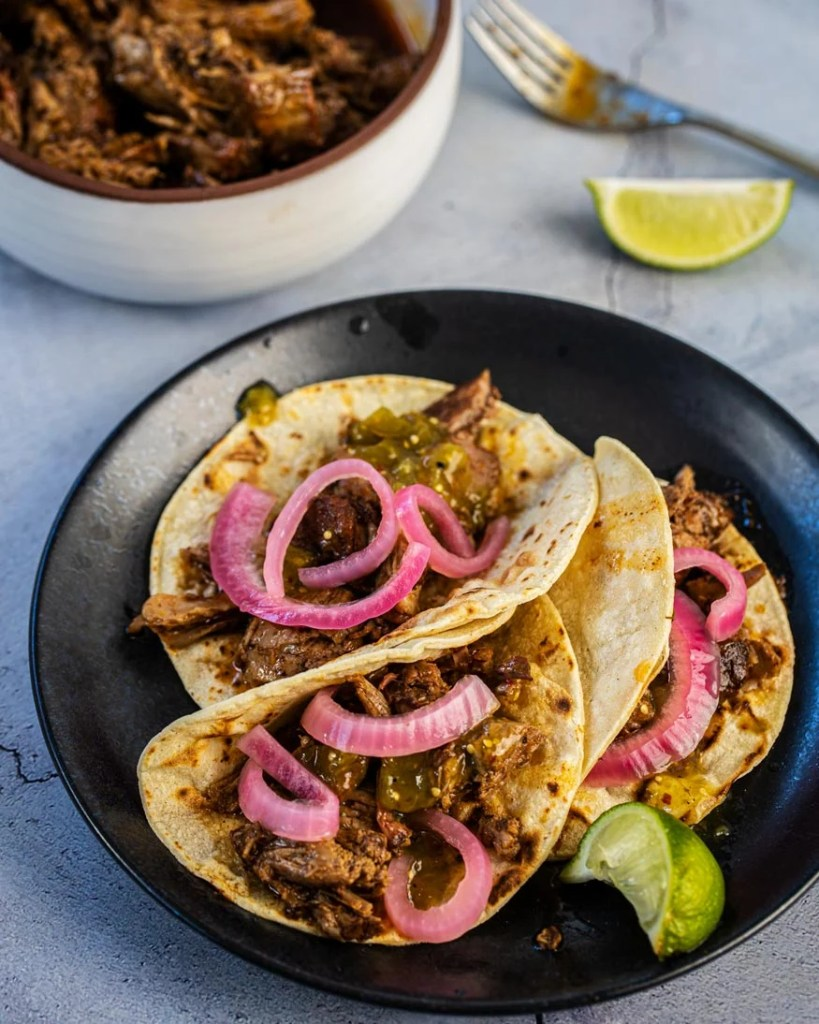 smoky lamb barbacoa tacos with salsa and pickled onions