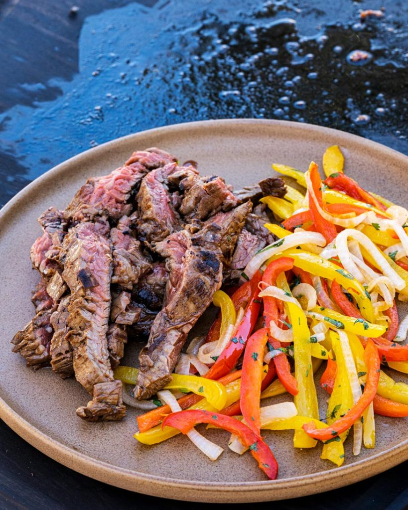 Skirt steak, peppers and onions for fajitas.
