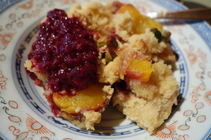 Peach crumble with purple raspberry-charapita-sauce