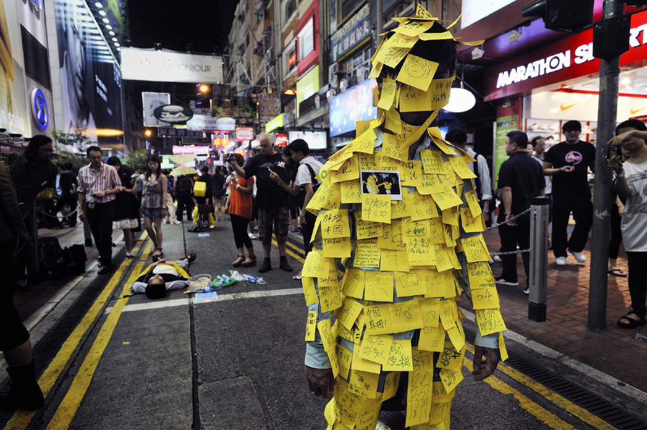 "Artists act out in street performances commemorating the June 4, 1989 Tiananmen Square demonstrations that ended in a bloody crackdown. A young man covered himself in sticky memo note paper that he had invited other artists and passers-by to inscribe with messages of protest, mostly to the Chinese government and their handpicked Hong Kong leadership. Among the messages inscribed: ""Free China,"" ""End Totalitarianism,"" ""Release Activists,"" ""Don't Be a Slave—Remember June 4,"" ""Investigate the Massacre,"" and ""Democracy Forever."" China's tolerance is wearing thin, but the adherence to the one country, two systems policy still allows the freedom for such expression in Hong Kong. If this were in China, these artist likely would already be in prison."