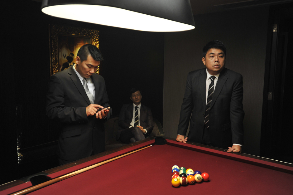 Actors playing a mainland gangster boss and two of his bodyguards rest between scenes of the Johnnie To film <em>Life Without Principle</em>.