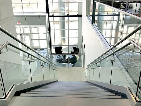 Commercial Stair Railings Demax Arch | Staircase Design For Commercial Buildings | Cylindrical Glass | Enclosed | Beautiful | Central Staircase | Sleek