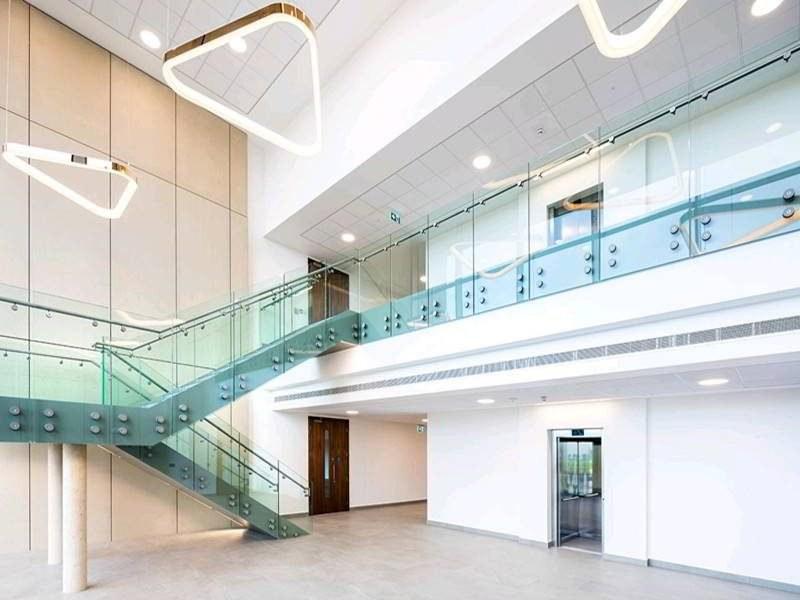 Standoff Glass Railing Demax Arch | Modern Staircase Glass Railing Designs | Commercial Building | Glass Panel Wooden Handrail | Side Glass Rail | Glass Stair | Modern Aluminium