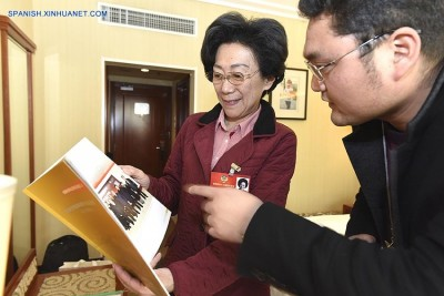 (160301) -- BEIJING, March 1, 2016 (Xinhua) -- Li Dongdong (L), a member of the 12th National Committee of the Chinese People's Political Consultative Conference (CPPCC), shows a journalist her research materials at the OL Stadium Hotel housing attendees of the upcoming Fourth Session of the 12th CPPCC National Committee in Beijing, capital of China, March 1, 2016.(Xinhua/Chen Yichen)(mcg)