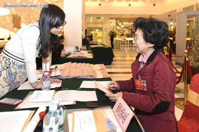 (160301) -- BEIJING, March 1, 2016 (Xinhua) -- Li Dongdong (R), a member of the 12th National Committee of the Chinese People's Political Consultative Conference (CPPCC), registers at the OL Stadium Hotel housing attendees of the upcoming Fourth Session of the 12th CPPCC National Committee in Beijing, capital of China, March 1, 2016.(Xinhua/Chen Yichen)(mcg)