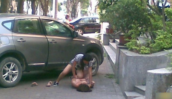 A Chinese wife attacks her cheating husband's girlfriend on a street in Guangzhou, China.
