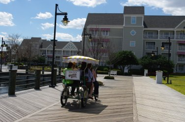 one of the Surrey bikes riding towards the Yacht Club on the Boardwalk
