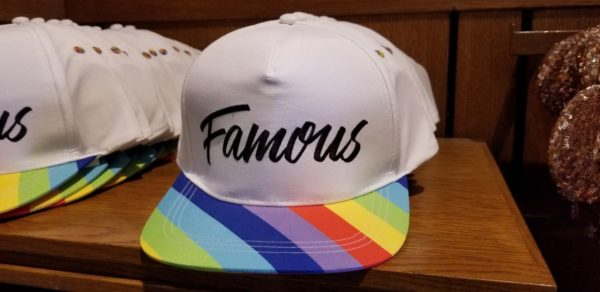 """3a3a1e56735 The crisp white cap has """"Famous"""" written accross the front in black script.  This cap is available in select Disney Parks ..."""