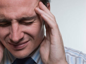 Man with migraine headache. Study shows chiropractic care can help.