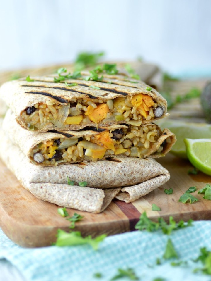 sweet potato black bean burritos stacked on each other on cutting board