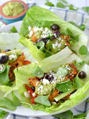 close-up of three Greek chicken lettuce wraps on white plate