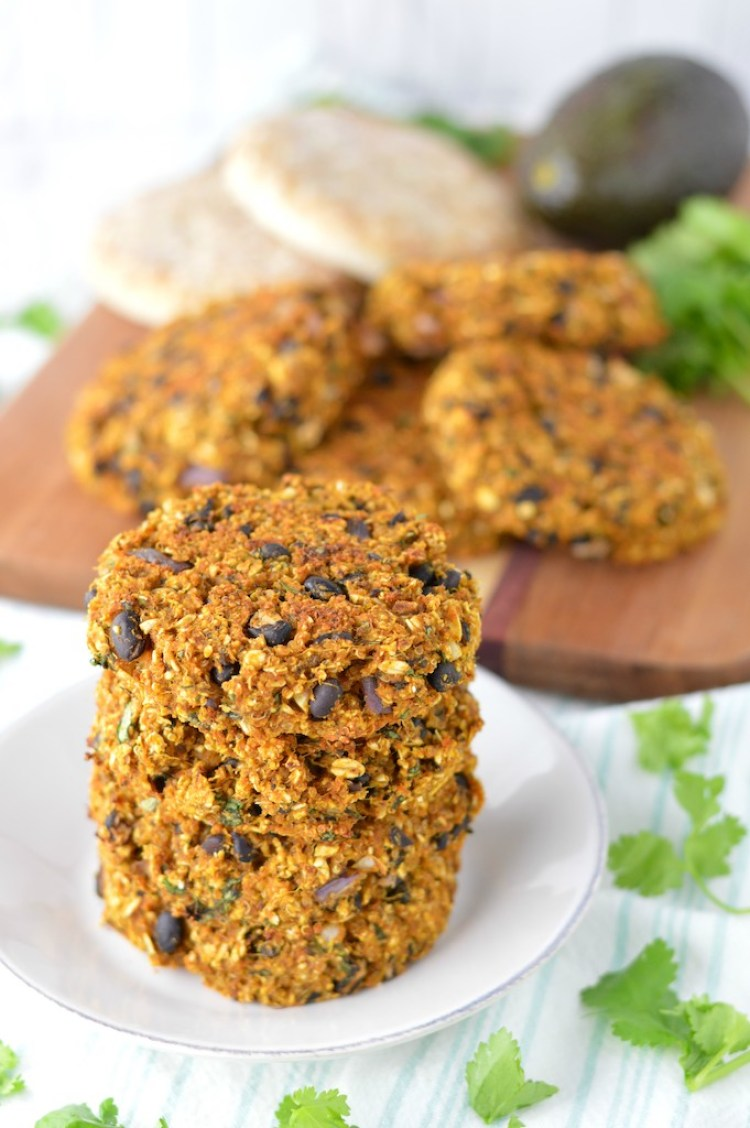 close-up of stacked sweet potato black bean burgers on white plate and cutting board