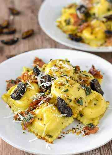 close-up of butternut squash and goat cheese ravioli on two white plates