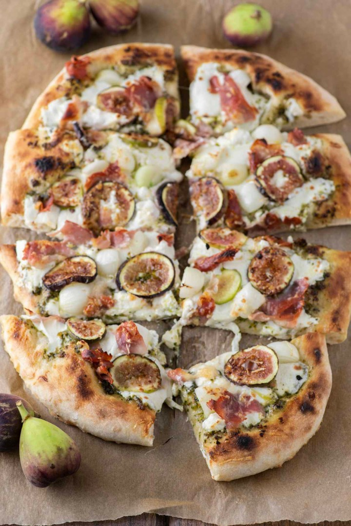 sliced up fig prosciutto pizza on parchment paper
