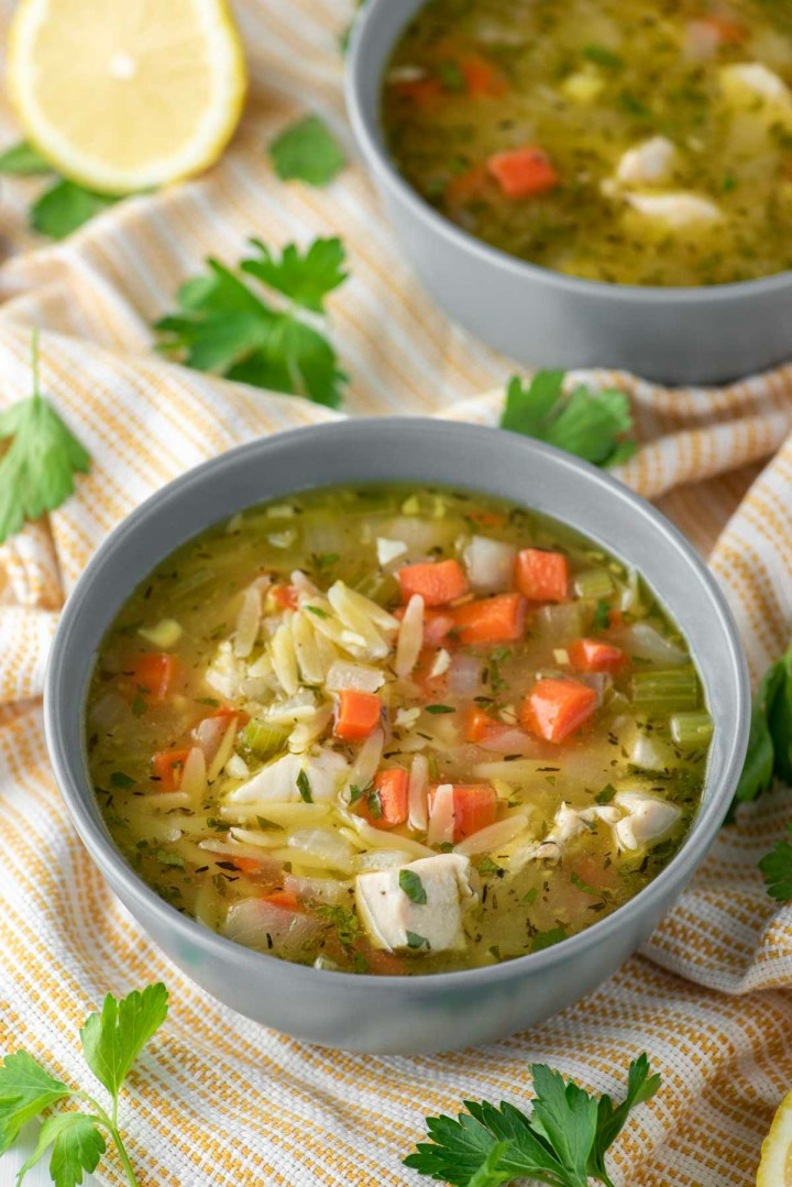 lemon chicken orzo soup in bowl on dish towel