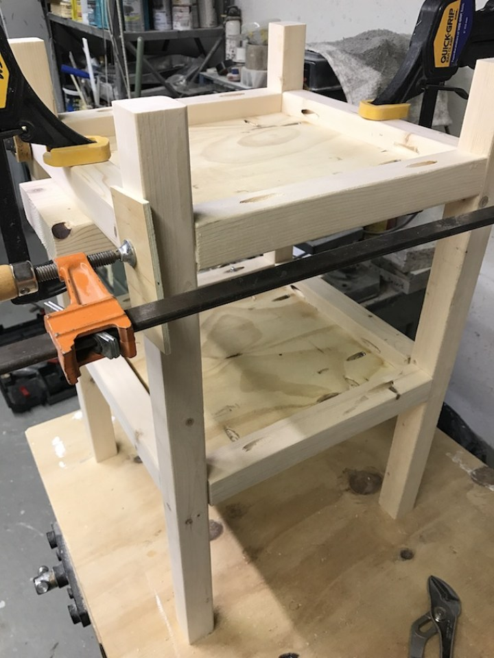 legs of table being clamped to shelves