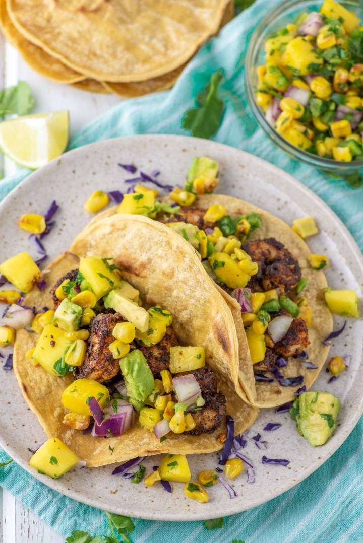 two spicy shrimp tacos on plate with bowl of corn mango salsa in background