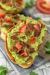 slice of bacon avocado toast on cutting board