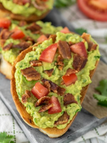 slice of bacon avocado toast on cutting board
