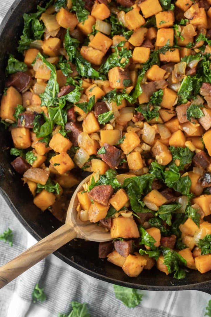 overhead shot of spoon dipped in chorizo sweet potato hash in skillet