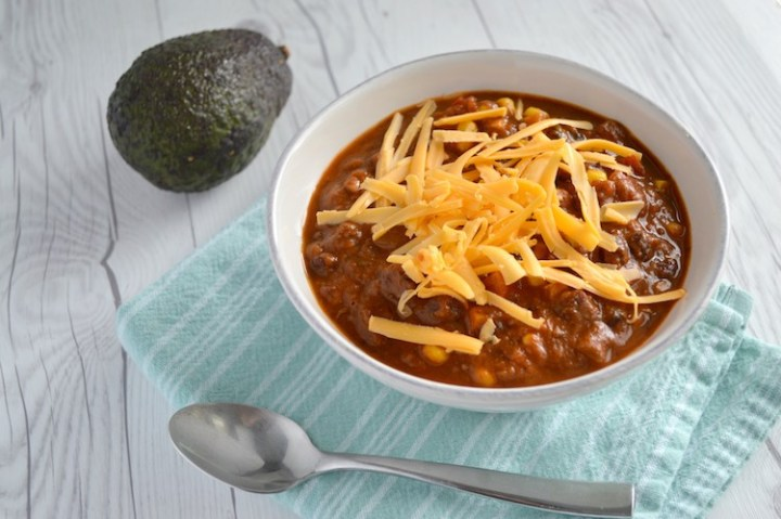Instant Pot vegetarian chili in white bowl with 1 avocado