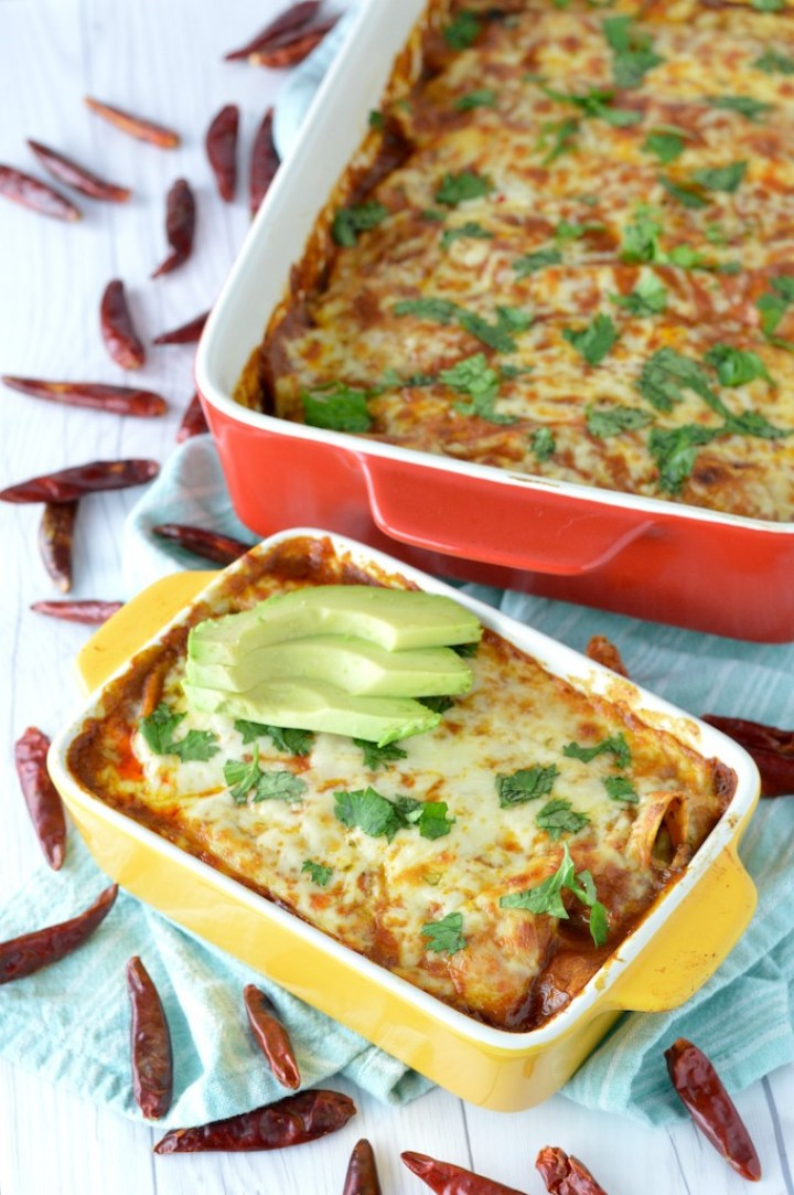vegetarian enchiladas in yellow baking dish with red baking dish in background